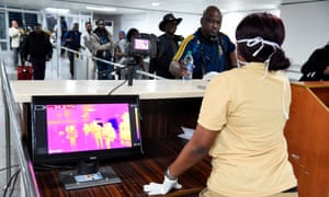 A Port Health Service staff member stands next to a thermal scanner as passengers arrive at Murtala Mohammed International airport in Lagos, Nigeria