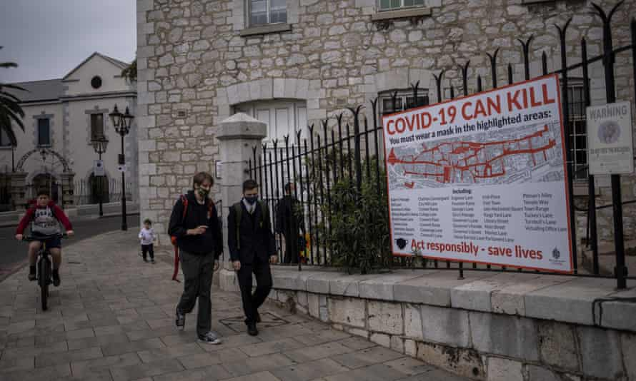 Schoolchildren walk by a Covid-19 information banner in Gibraltar.