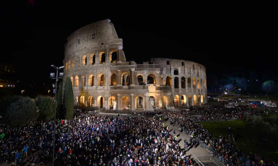 People gather for the Via Crucis (Way of the Cross) torchlight procession on Good Friday at the Colosseum.