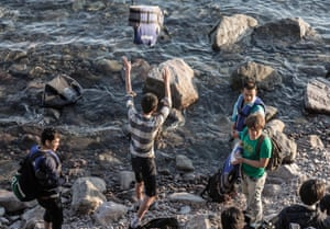 A group of young men dispose of their life jackets as their rubber dinghy makes it to shore in Molyvos