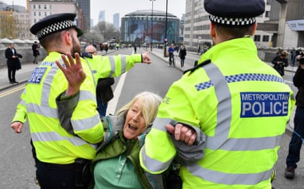 Police officers remove an Extinction Rebellion activist from Waterloo Bridge.