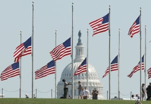 A National Park Service worker lowers US flags to half mast on the grounds of the Washington Monument