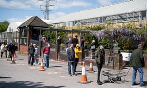 People observe physical distancing rules as they queue outside a garden centre in Cardiff.