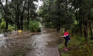 A person is seen next to the overflowing Nepean River at the Penrith weir on Saturday.