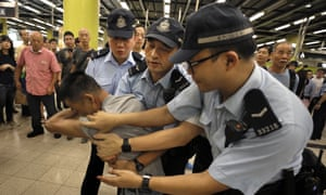 Police restrain a passenger who tried to fight with protesters on the Hong Kong subway, 30 July 2019