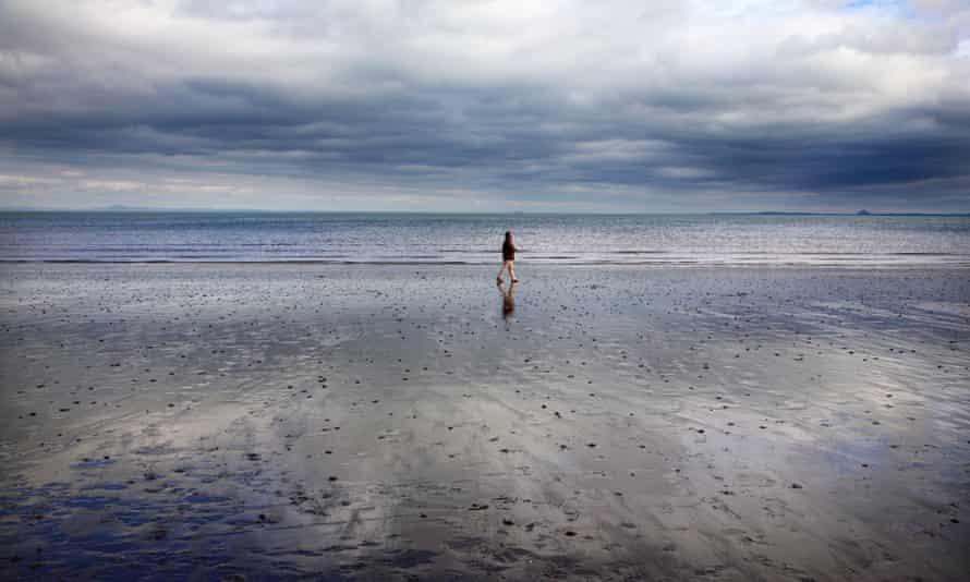 A man walking on Portobello beach in Edinburgh.