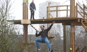A visitor slides down a zipwire at the Go Ape experience which has just opened in Battersea Park.