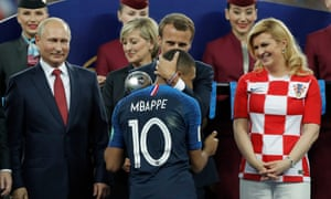 French president Emmanuel Macron kisses the head of Kylian Mbappé as he presents him with the best young player of the tournament award.