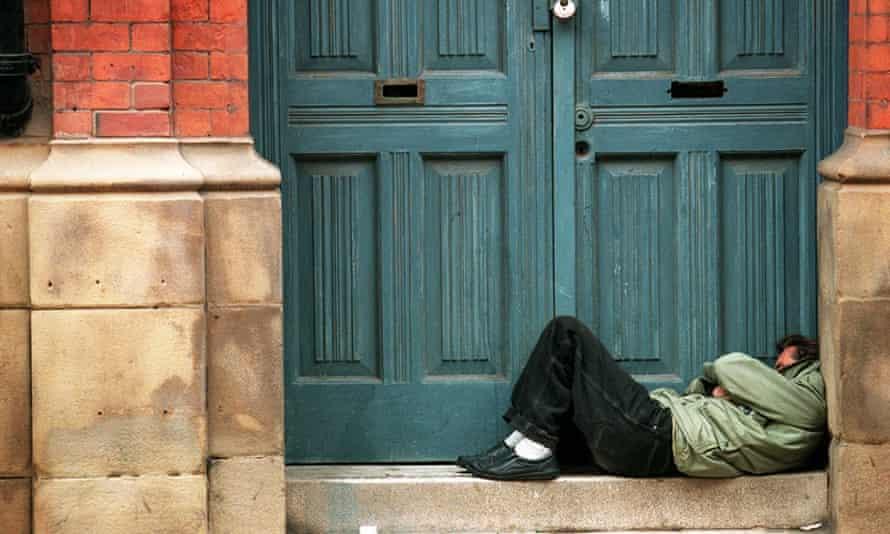 A homeless man sleeps in a doorway.