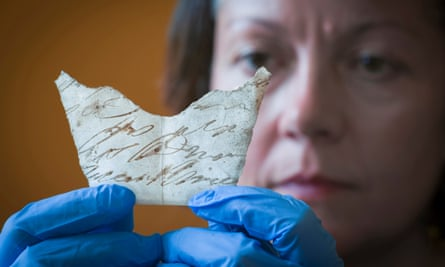 Curator Anna Forest examines a fragment of an 18th-century handwritten document discovered under the floorboards of Oxburgh Hall, Norfolk.