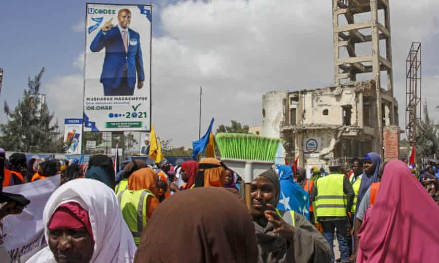 Somalis walk past a billboard showing a presidential candidate Omar Abdulkadir Ahmedfiqi in Mogadishu.