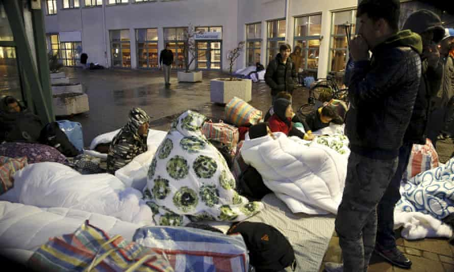 Refugees sleep outside the entrance of the Swedish migration agency's arrival centre for asylum seekers in Malmo