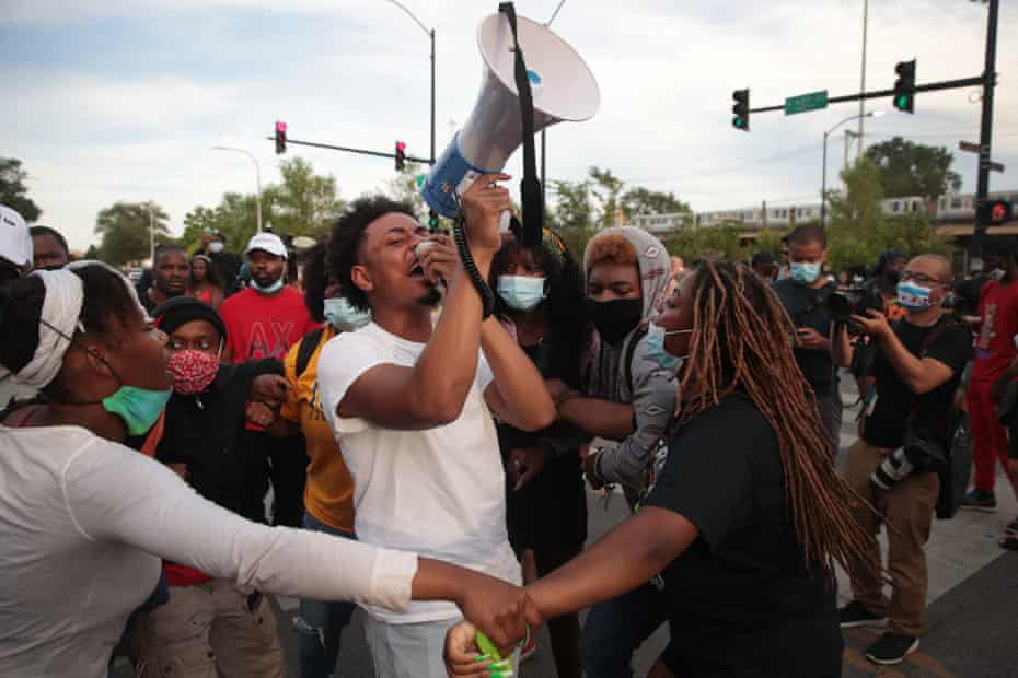 Demonstrators protest outside a police station on 11 August in Chicago in response to a shooting of a 20-year-old man who allegedly fired at officers in the Englewood neighborhood.