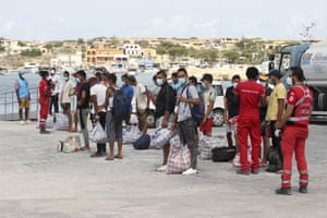 Migrants wait to board a coastguard ship that will take them to the GNV Rhapsody ferry moored off Lampedusa island, Italy, Saturday 5 September 2020.