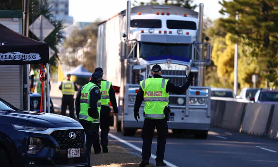 Queensland police stop trucks at the border in Coolangatta on Wednesday. The Queensland government has further tightened border restrictions for people travelling into the state from NSW.