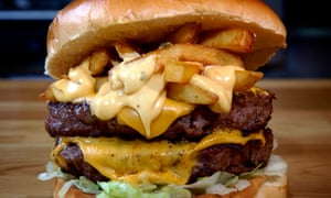 Close up of a burger and cheese with chips  - the chips are inside the burger bun.