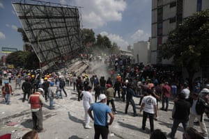 Rescue workers and volunteers stand in the streets surrounded by carnage.