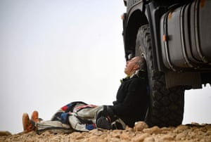 Biker Pascal Rauber of Team 2RM rests at the foot of a truck