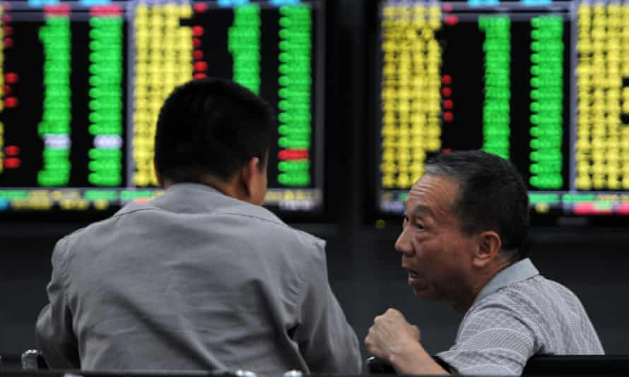 Investors monitor stock prices at a securities company in Jiujiang in China's central Jiangxi province.
