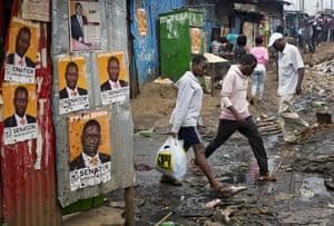 Nairobi, Kenya: Residents walk past election posters in the Kibera slum
