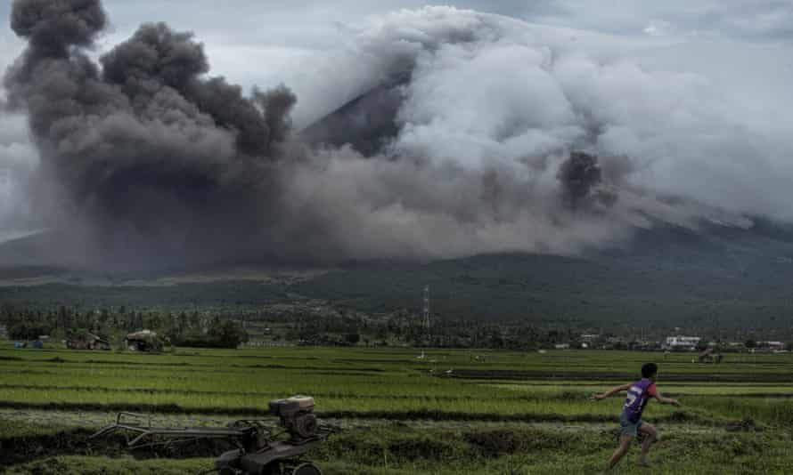 A boy in Camalig, Philippines, runs as pyroclastic clouds erupt from the Mayon volcano.