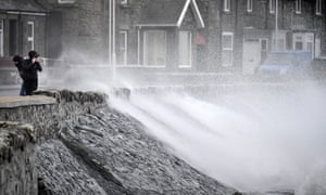 Waves crash against the harbour wall in Port William, Scotland