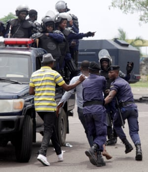 Congolese policemen detain an opposition activist who was taking part in the march