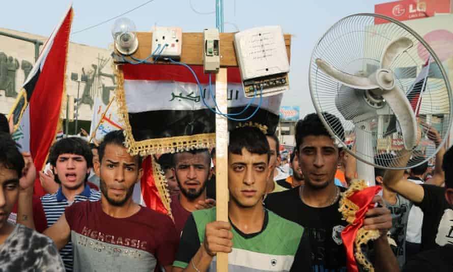 Protesters carry national flags and a fan in Baghdad on Friday