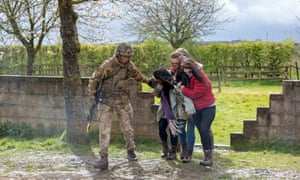 Three women are led to safety during a demonstration in Salisbury Plains by infantry.