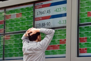 A businessman watches a share prices board in Tokyo today.