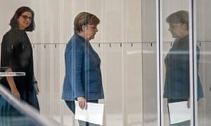 Angela Merkel is followed through a glass corridor by the Green party co-leader Katrin Göring-Eckardt