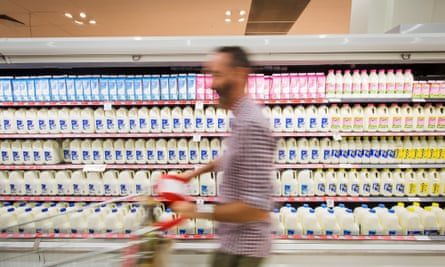 A shopper walks past bottles of milk displayed in the dairy section of a Coles supermarket