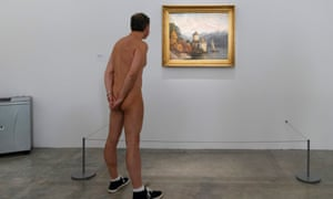 A naked man looks a a picture in a Paris art gallery