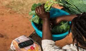 A mobile phone charged using M-Kopa solar technology rests on loaf of bread as a girl prepares food in a basin in Ndela village, Machakos county in Kenya