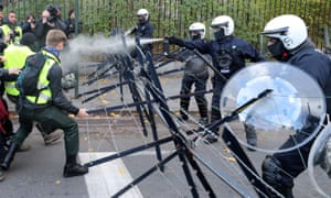 Police spray tear gas during clashes with protesters in Belgium.
