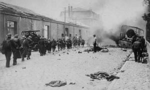 British soldiers march through a street in Dunkirk as it is heavily bombed in an attempt by the Germans to take the town before the evacuation of the allied forces