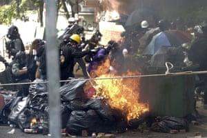 Activists run past burning debris