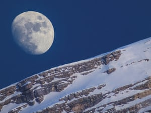 <strong>Moon and Antelao </strong> Late afternoon at San Vito di Cadore, Italy the moon shines over Monte Antelao. The snow-covered dolomite ridge of the mountain and the Earth's only natural satellite bear a striking resemblance to one another, contrasting against the bright blue of the afternoon sky