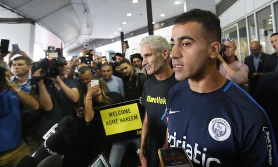 Former Socceroo Craig Foster (centre) with refugee footballer Hakeem Al-Araibi (right) as he arrives at Melbourne International Airport.