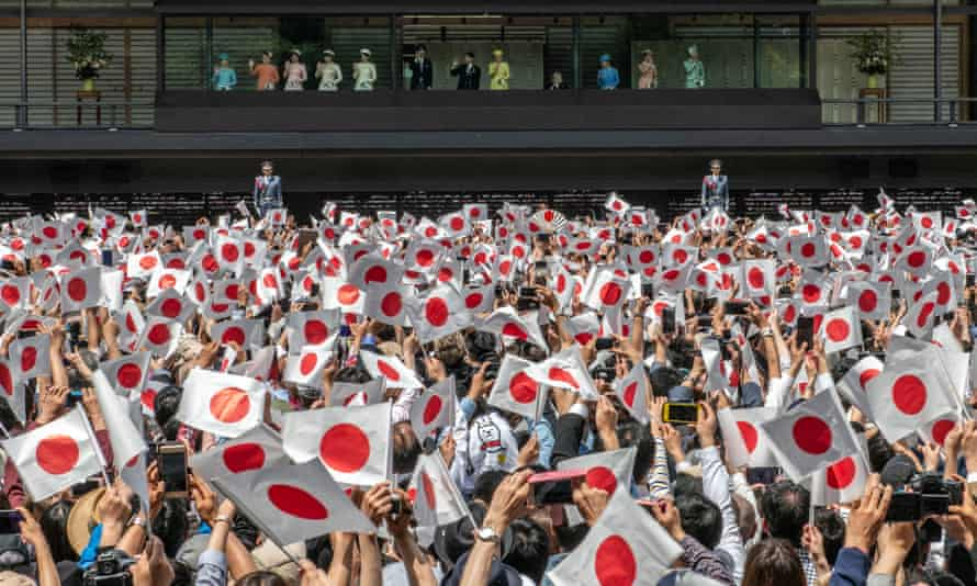 A sea of red and white: the crowd waves Japanese flags as the imperial family appears at the balcony