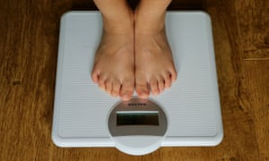 A child measures their weight on scales.