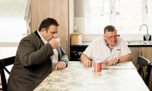 Two men drink tea in kitchen
