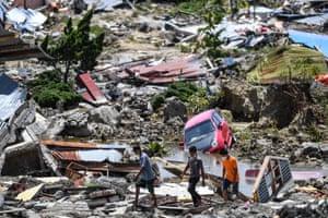 Residents walk through debris in Perumnas Balaroa village in Palu.