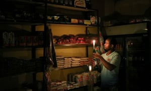 An owner of a convenience store, or 'spaza shop', picks an item for a customer as he holds a candle after a power cut in Soweto, South Africa.