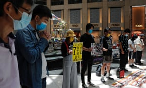 Pro-democracy protesters in Hong Kong hold a minute's silence on Tuesday after China's parliament passed the national security law.