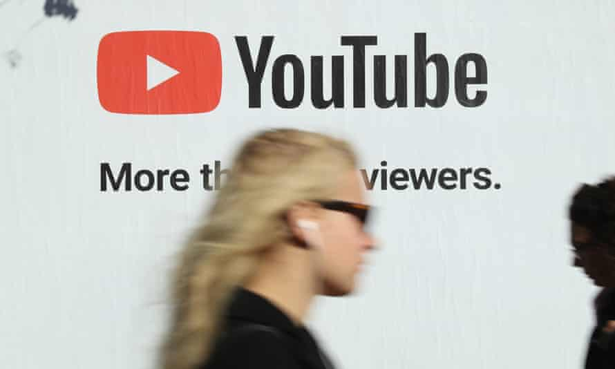 A woman walks past a billboard advertisement for YouTube