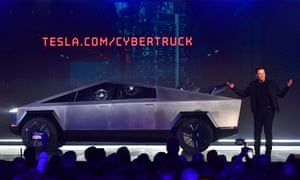 Tesla co-founder and CEO Elon Musk speaks next to the newly unveiled Tesla's Cybertruck, with shattered windows after a failed resistance test.