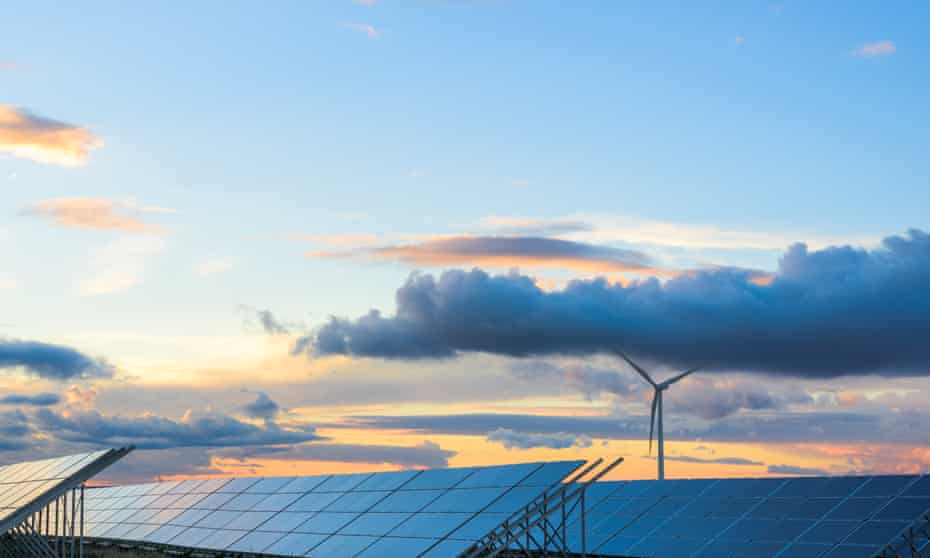 Solar panels and wind turbine at sunset