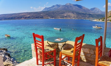 A table for two on a terrace overlooking the sea and, in the distance, mountains in Greece. To promote a food tour of Greece by Intrepid Travel.