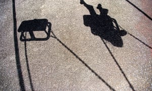 The shadow of a young girl or boy playing on a swing